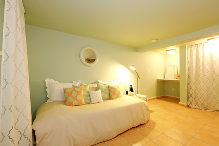 Green basement room with white sofa with tile floor  photo