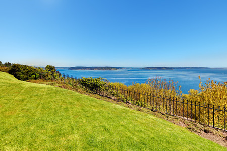 tacoma: Water view of Puget Sound and hill with grass. Private yard in Tacoma, WA. Stock Photo