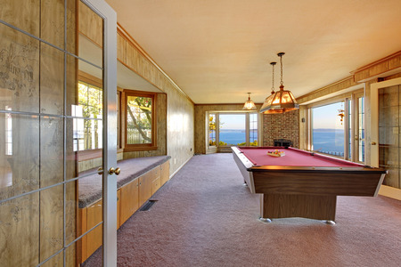 pool table: Large old room with pool table, window bench and water view.