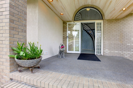 trims: Entrance porch with glass door. Porch decorated with statue and large stone flower pot