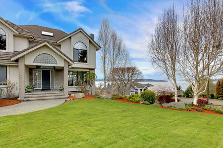 northwest: Luxury house exterior with flower beds and lawn. Water view