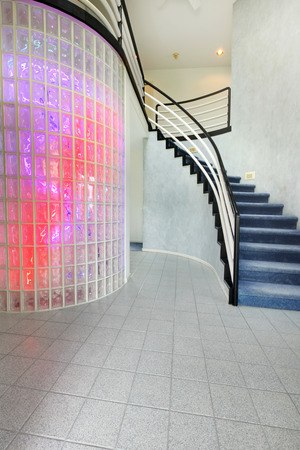 Modern foyer with glass block wall trim in multi color lights. View of staircase photo