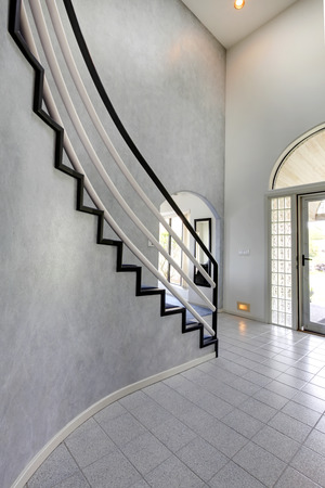 foyer: Modern foyer with high ceiling and tile floor. View of steep staircase with black and white railings Stock Photo