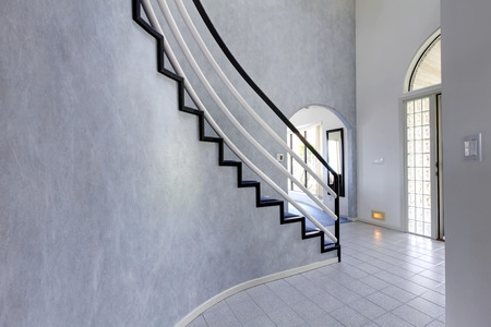 Modern foyer with high ceiling and tile floor. View of steep staircase with black and white railings photo