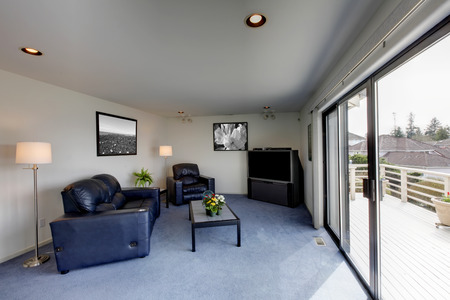Cozy living room with black leather furniture set and walkout deck 版權商用圖片