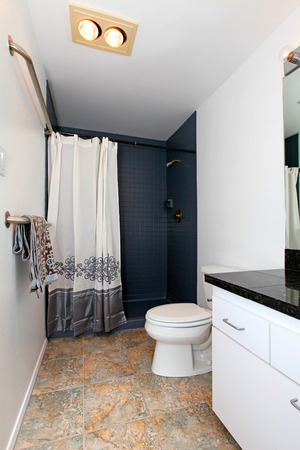modern bathroom design: White bathroom with tile floor and tile wall trim. Decorated with towels and curtain Stock Photo