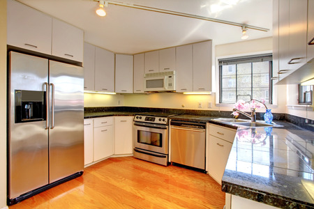 appliances: Simple kitchen interior with white storage combination and steel appliances.