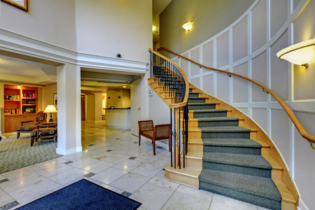 Foyer with columns and wooden staircase. Open floor plan. photo