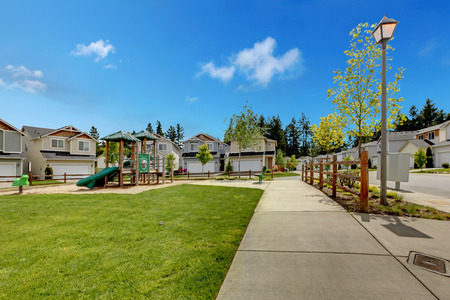 Houses with playground for kids and green lawn photo