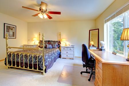 nightstands: Bedroom with antique high poles bed, nightstands and desk.