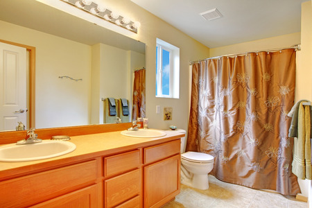 Light tones bathroom with honey cabinet, tile floor and bath tub with brown curtain Stock Photo - 29001773