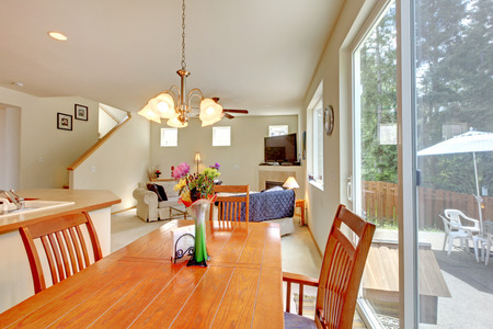 Dining area with brown table set and slide doors to walkout deck. View of living room Stock Photo - 29001777
