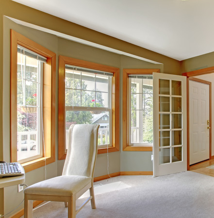 french doors: Olive walls room with light tone carpet floor. View of windows with white elegant chari and open french door Stock Photo