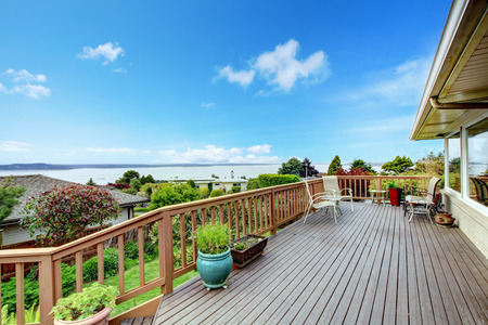 patio chairs: Wooden walkout deck with patio table and water view.