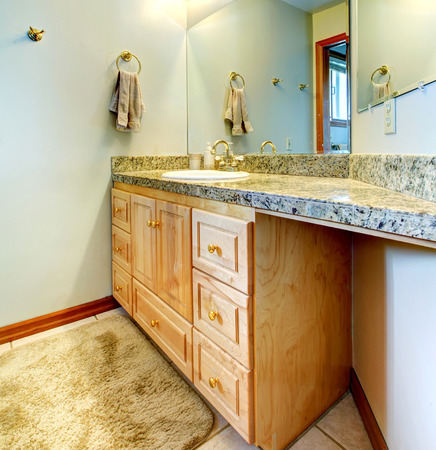 Aqua color walls bathroom with tile floor and rug. View of bathroom vanity cabinet with mirror Stock Photo - 29033022