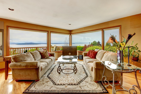 view of an elegant red couch: Beautiful living room with atnique glass top tables, sofas and chest. Room has water view through the window