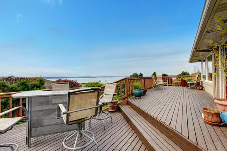 Wooden walkout deck with patio table and water view.