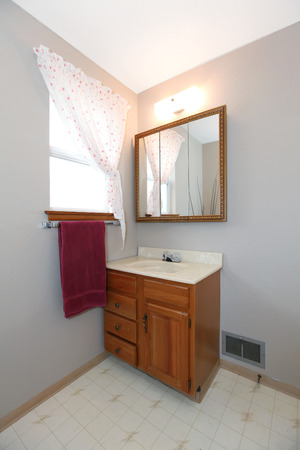 Simple bathroom corner with bathroom vanity, mirror, window treated with light curtains and burgundy towel Stock Photo - 29090673