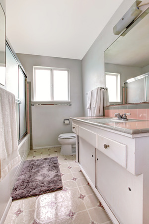 rug: White bathroom with old vanity cabinet, linoleum and soft rug Stock Photo