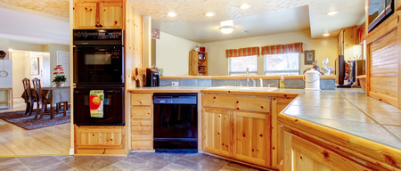black appliances: Rustic kitchen interior with tile floor, honey storage cabinets and black appliances