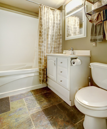 White and brown bathroom with tile floor and white tub, toilet and antique bathroom vanity Stock Photo - 29090770
