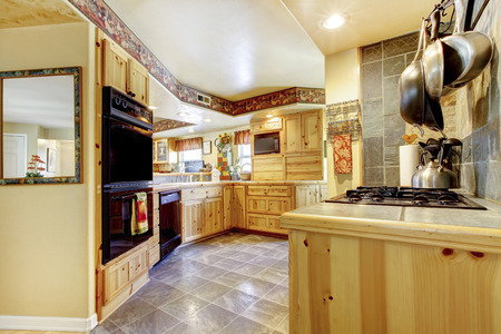 Rustic kitchen with gold wooden cabinets, black appliances and tile floor photo