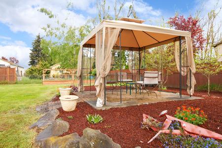 Backyard with flower beds, lawn and gazebo