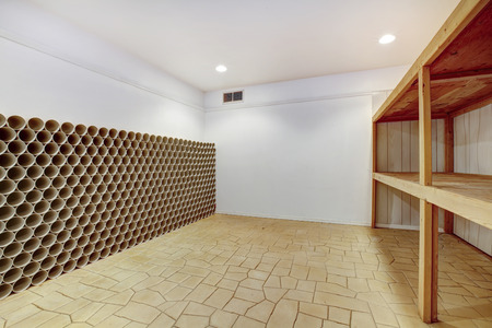 wood ceiling: Empty wine cellar with wooden shelves and wine storage unit Stock Photo