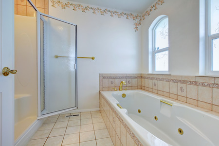 white trim: White refreshing bathroom with white whirlpool, glass door shower, tile floor and wall trim