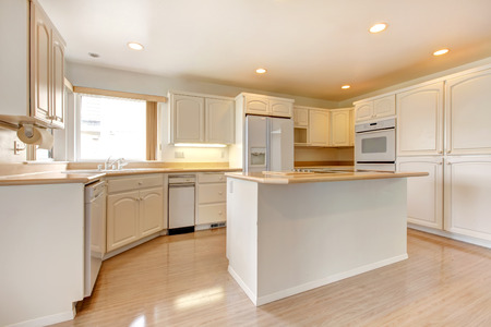 open plan: Modrn kitchen room with shiny hardwood floor, white cabinets and appliances. View of kitchen island