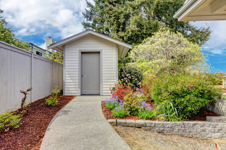 sheds: Backyard with small shed, walkway and colorful flower bed along side