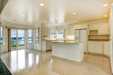 open floor plan: Shiny new kitchen room with light tones cabinets and kitchen island. Room has walkout deck