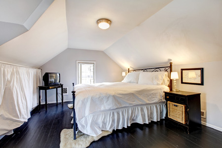 nightstand: White velux bedroom with vaulted ceiling and old black hardwood floor. Furnished with iron frame bed, nightstand and tv