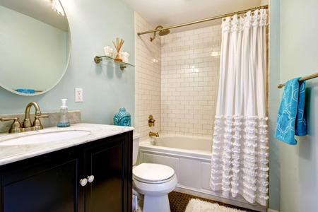 アクアのバスルームには暗い床とタイル壁のトリム。浴室の虚栄心のミラーとビュー