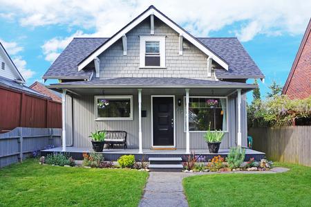 Pequeno antiga casa com pórtico de entrada decorado com antiguidades banco. Jardim da frente tem gramado e canteiros de flores