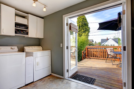 Laundry room with old appliances. View of walkout deck through open doors Stock Photo
