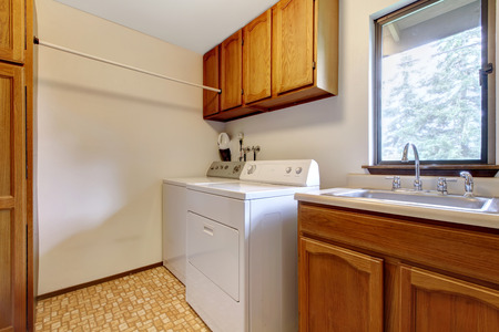 laundry room: Bright laundry room with wooden cabinets and white appliances