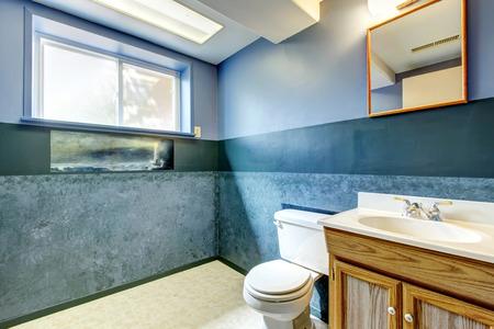bathroom mirror: Empty bathroom with dark navy walls, View of old wooden bathroom vanity and toilet