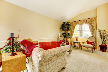 vaulted: Ivory living room with high vaulted ceiling and carpet floor. Furnished with antique sofa and chairs Stock Photo