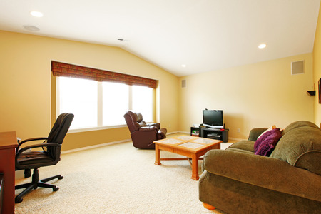 cofffee: Living room with vaulted ceiling and ivory walls. Furnished with old sofa, leather chair and wooden cofffee table
