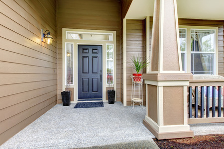 Entrance porch with black door, column and railings. Porch decorated with flower pots photo
