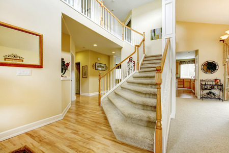View of elegant staircase with wooden white and brown railings in modern large house photo