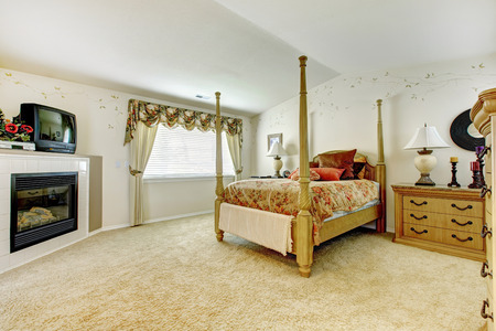 Spacious bedroom with vaulted ceiling. Room has fireplace and antique high pole bed. photo