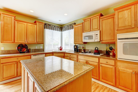 Bright kitchen room with honey color storage combination with white appkiances. View of kitchen island Stock Photo - 29378883