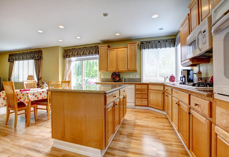 SImple yet practical kitchen interior. View of storage cabinets with kitchen island and dining area with walkout deck Stock Photo - 29378884