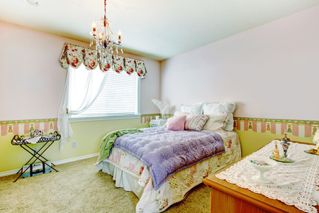 view of a comfortable bedroom: Comfortable bedroom with walls in pink and lime colors. View of bed with colorful bedding