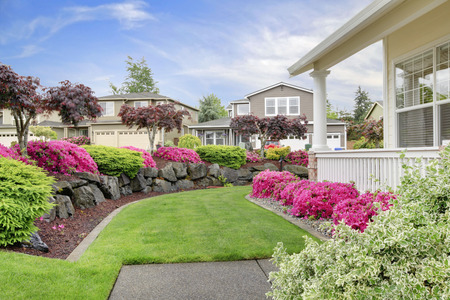 White house porch with blooming bushes and lawn. Beautiful landscape design