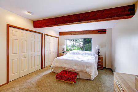 Bedroom in white color. Room has bright brown ceiling beams. photo