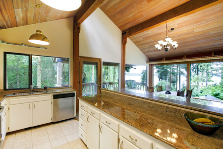 log cabin: White kitchen room with steel appliances and high vaulted ceiling. Kitchen room has walkout deck