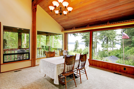 vaulted ceiling: Spacious dining area in log cabin house with high vaulted ceiling and wide window. View of rustic dining table set. Stock Photo